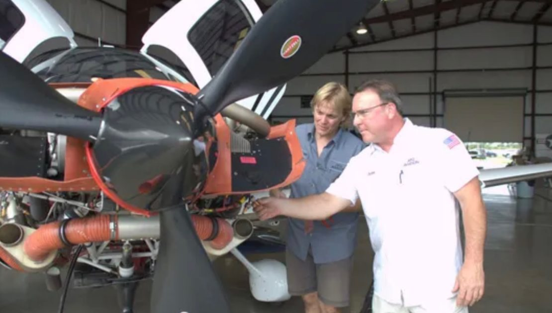 two people looking at the propeller of a plane